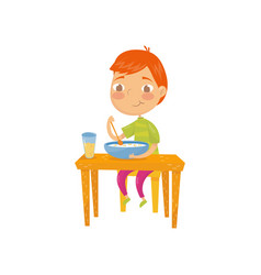 Cute red-haired boy sitting at table and eating vector