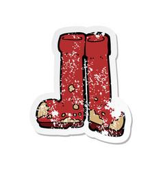 Retro distressed sticker of a cartoon muddy boots vector