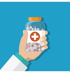 Medicine bottle with red cross in hand of a doctor vector