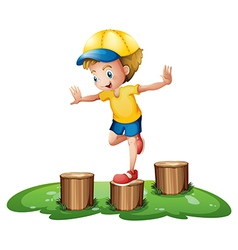 A smiling boy playing with the stumps vector image
