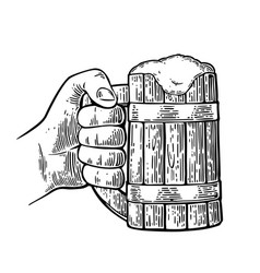 Male hand holding full beer wooden mug with foam vector