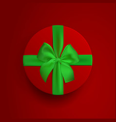 Red round box with green ribbon and bow isolated vector
