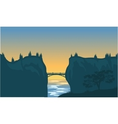 Silhouette of bridge and cliff vector