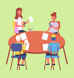 kids sitting at a table and cutting white paper vector image