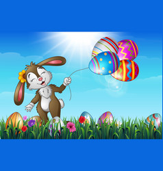 smiling easter bunny holding colorful easter eggs vector image