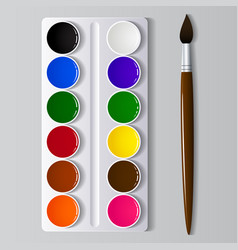 Watercolor paints in a box with a brush vector