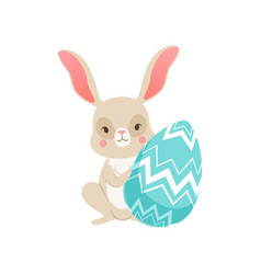 cute cartoon bunny sitting holding blue egg funny vector image