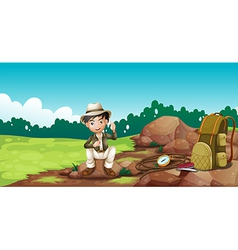 A boy wearing a hat sitting on a rock vector image