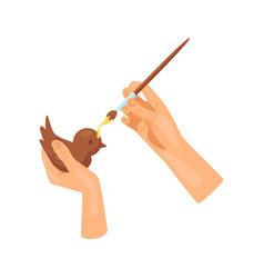 Hands decorate wooden figure of bird with yellow vector