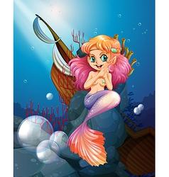 A pretty mermaid under the sea near the rocks vector