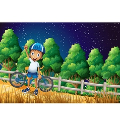 a happy boy with a bike standing at woods near vector image