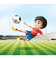 A boy playing soccer in the soccer field vector image