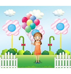 A girl holding balloons in the garden vector image