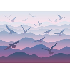 silhouettes of flying birds over mountains vector image