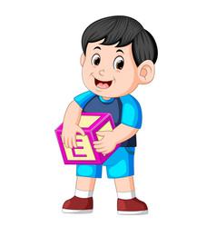cute boy holding alphabet cube vector image