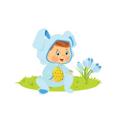 baby boy in bunny costume with decorative egg vector image