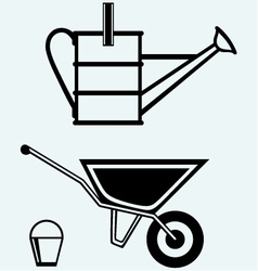 Garden wheelbarrow and watering can vector image vector image