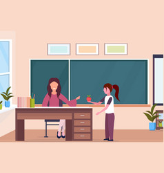 schoolgirl giving apple to woman teacher sitting vector image