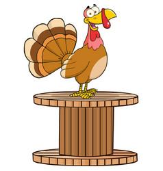 Happy turkey bird character on a giant spool vector