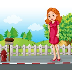 A woman at the roadside near the wooden mailbox vector image