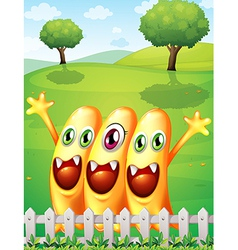 Three happy orange monster near the fence vector