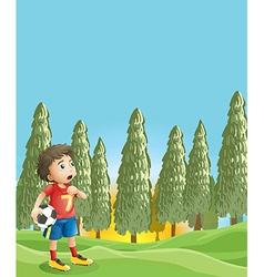A young boy holding a soccer ball near the pine vector image vector image