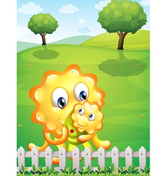 An orange monster carrying her baby monster at the vector image