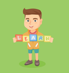 Boy holding blocks that spelling the word learn vector