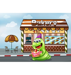 A monster with a cake near the bakery vector