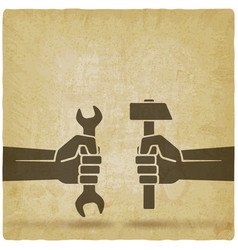 hands holding hammer and wrench on vintage vector image