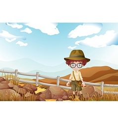 A serious explorer standing near the rocks vector image