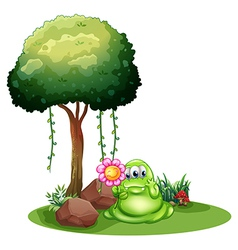 A monster holding a flower standing near the tree vector image vector image