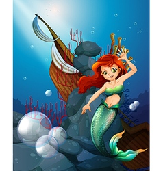 A sea with a mermaid near the wrecked boat vector