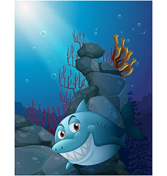 A smiling shark under the sea near the rocks vector image