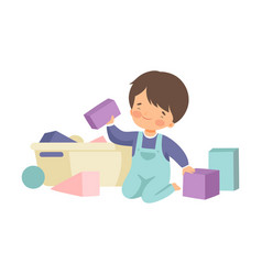 Cute boy sitting on floor and cleaning up his toys vector