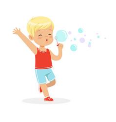 cute little blonde boy blowing bubbles vector image