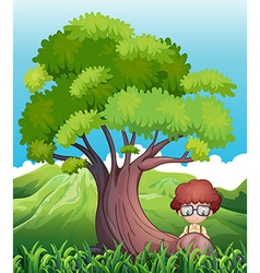 A young boy near the roots of the giant tree vector image