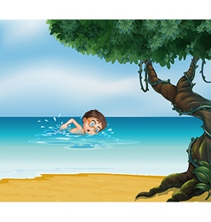 A boy swimming at the beach with an old tree vector image