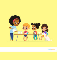 smiling multiracial children sit at table and have vector image