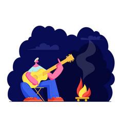 man sitting at campfire at night playing guitar vector image