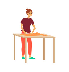 woman standing at table and cutting fabric by vector image