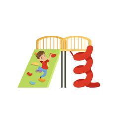 Cute little boy climbing wall on playground vector