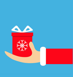 santa claus hand holding gift box with bow snow vector image