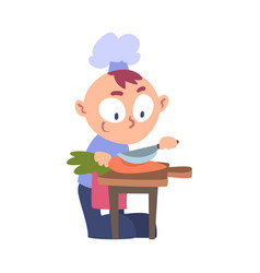 Boy chef cook cutting carrot with knife cute vector
