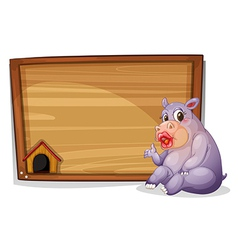 A hippopotamus sitting beside a blank wooden board vector image