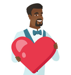 Young african-american groom holding a big heart vector