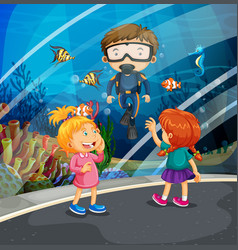 Girls looking at fish and diver in the aquarium vector