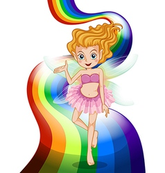 A fairy standing at the rainbow vector image