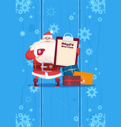 Santa claus hold present list on happy new year vector
