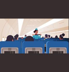 stewardess explaining passengers how to use seat vector image